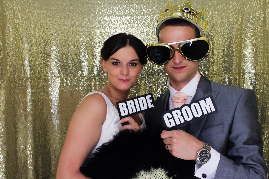 Bride and groom in the gold photo booth